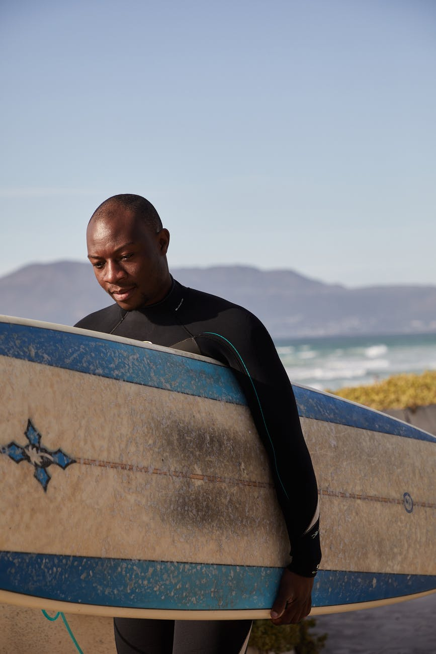 pondering black surfer carrying surfboard on sea shore