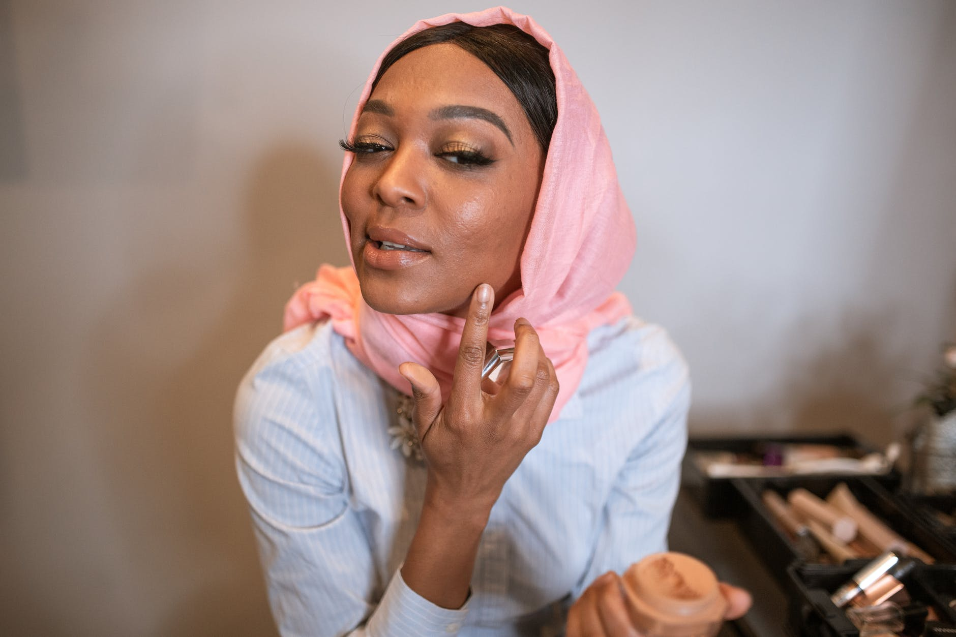 woman in white long sleeve shirt and pink hijab applying make up